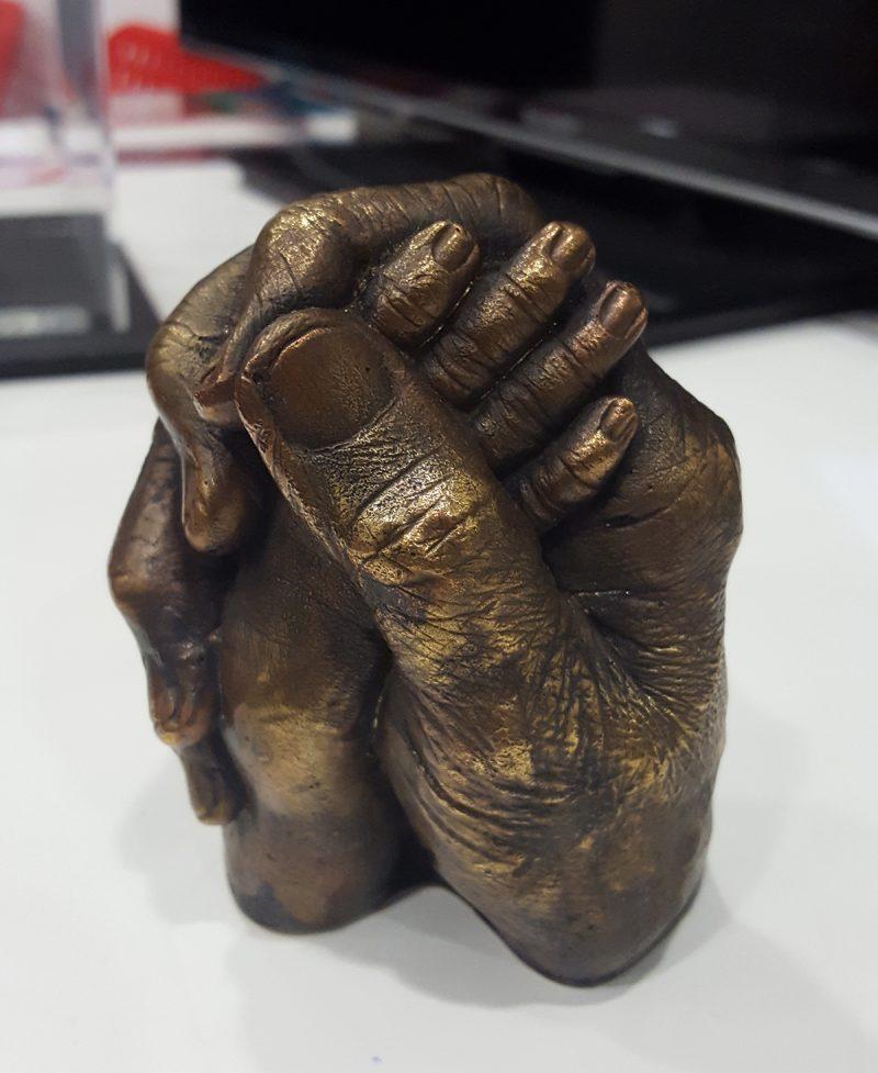 Bronze statue parent and child hands